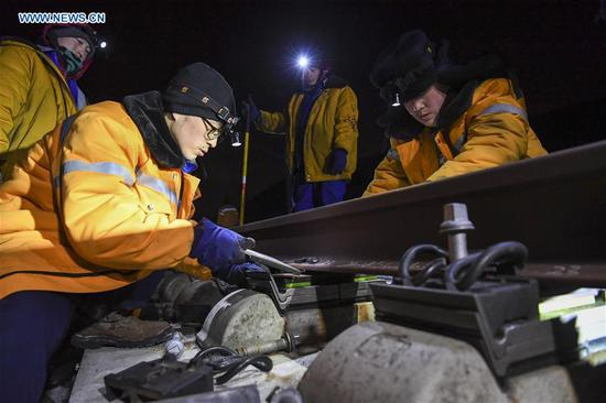 Workers check the quality of rail at the Xinjiang section of Lanzhou-Xinjiang high-speed railway in Urumqi, northwest China's Xinjiang Uygur Autonomous Region, Feb. 5, 2018. Engineers examine the rail every night to ensure the safety of trains and passengers. (Xinhua/Hu Huhu)