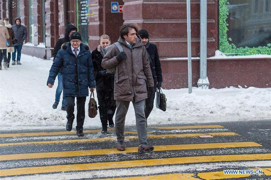People cross a street in Moscow, Russia, on Feb. 5, 2018. Moscow experienced a record strong snowfall last week, which caused delays and cancellations of air flights and the death of at least one victim, officials said.