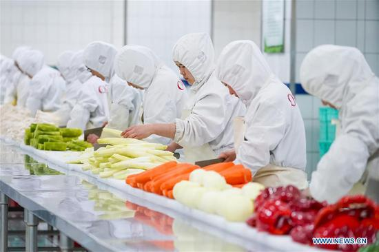 Workers deal with vegetables for set meals on high-speed trains at a food production base in Beijing, capital of China, Feb. 7, 2018. Altogether 18 kinds of set meals at 6 price levels are available on China's high-speed trains during the Spring Festival travel rush which is from Feb. 1 to March 12. (Xinhua/Shen Bohan)