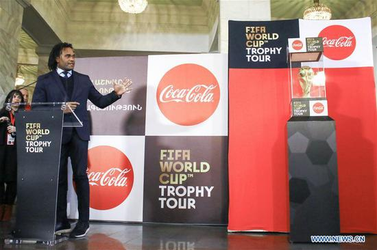 Former French player Christian Karembeu (L) gestures as he presents the FIFA World Cup Trophy during a ceremony in Yerevan, Armenia, on Feb. 7, 2018. The FIFA World Cup trophy arrived in Yerevan on Wednesday as part of its worldwide tour ahead of the 2018 FIFA World Cup to be staged in Russia. (Xinhua/Gevorg Ghazaryan)