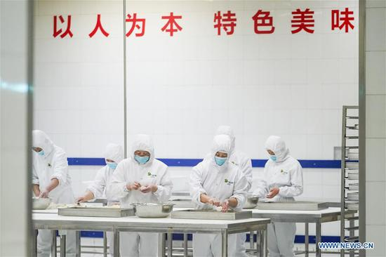 Workers make steamed buns in the preparation of set meals for high-speed trains at a food production base in Beijing, capital of China, Feb. 7, 2018. Altogether 18 kinds of set meals at 6 price levels are available on China's high-speed trains during the Spring Festival travel rush which is from Feb. 1 to March 12. (Xinhua/Shen Bohan)