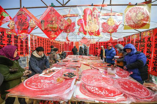 People select Spring Festival goods at a grand fair in Yingkou City of northeast China's Liaoning Province, on Feb. 8, 2018, the day of Xiaonian (small year). Xiaonian falls on the 23rd or 24th day of the last month of the Chinese traditional lunar calendar, marking the start of the countdown to Spring Festival. (Xinhua/Pan Yulong)