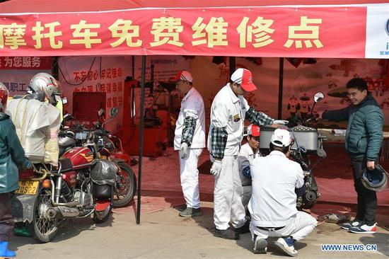 Volunteers repair motorcycles for migrant workers at Fengkai service station, south China's Guangdong Province, Feb. 8, 2018. Many migrant workers in China chose to go home by motorcycle for a family reunion in the Spring Festival, or Chinese traditional lunar New Year. (Xinhua/Liang Xu)