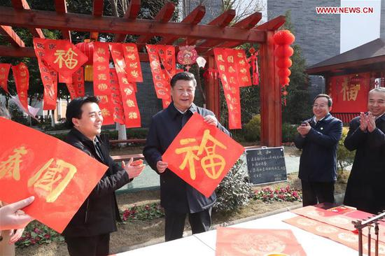Chinese President Xi Jinping (2nd L), also general secretary of the Communist Party of China Central Committee and chairman of the Central Military Commission, shows a Chinese character