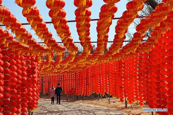 People walk under red lanterns in Changshanzhuang Village of Mamuchi Township in Yinan County, east China's Shandong Province, Feb. 13, 2018. Different cities around China were decorated to greet the upcoming Chinese Lunar New Year. (Xinhua/Shi Lianying)