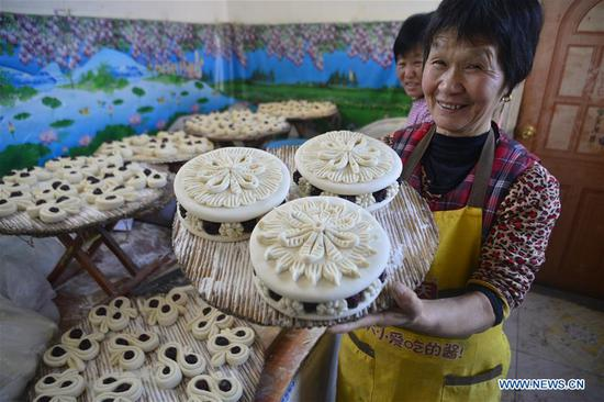 Villager Zhang Shuju displays steamed buns at Xiaozhuang Village of Jiazhai Town in Chiping County of Liaocheng City, east China's Shandong Province, Feb. 13, 2018. Steamed bun with colorful patterns, a kind of traditional food in some parts of China, is usually made during the Spring Festival to convey the meaning of better life. (Xinhua/Zhao Yuguo)