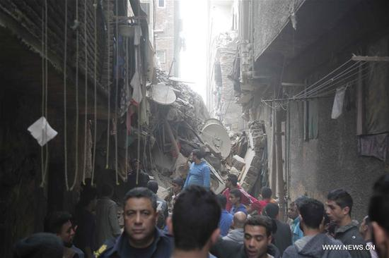 People gather at a building collapse site in Manshiyet Nasser area of Cairo, Egypt, on Feb. 22, 2018. A three-year-old child died and 16 people were injured in the collapse of a four-storey building in Cairo's Manshiyet Nasser area earlier today, according to ahramonline. (Xinhua)