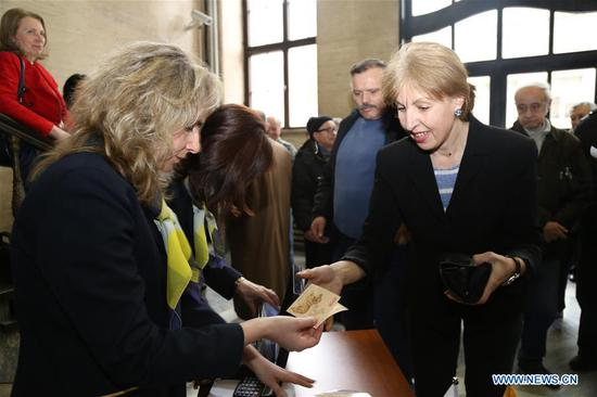 A woman buys copies of the postage stamp
