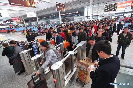 Passengers go to board a train at the Guiyangbei Railway Station in Guiyang, capital of southwest China's Guizhou Province, March 1, 2018. Guiyang railway was expected to witness a travel peak of 110,000 passengers on Thursday, one day before the Lantern Festival. (Xinhua/Liu Xu)