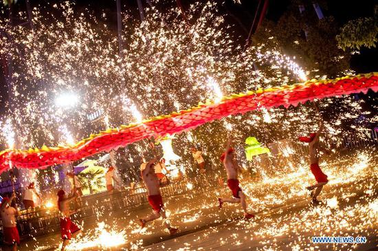 People perform fire dragon dance in shower of molten iron sparkling like fireworks to greet the upcoming Lantern Festival at the Wuhan Happy Valley in Wuhan, capital of central China's Hubei Province, Feb. 28, 2018. The Lantern Festival falls on the 15th day of the first lunar month, or March 2 this year.(Xinhua/Xiong Qi)