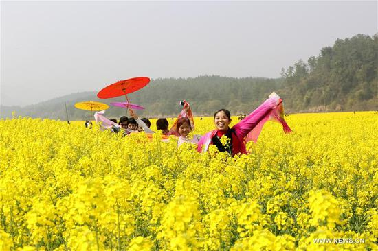 Tourists pose for photos amid cole flowers at Fengping Village of Jishui County, east China's Jiangxi Province, March 3, 2018. (Xinhua/Liao Min)