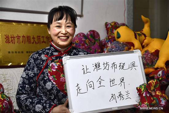 Sun Xiulan, an inheritor of intangible cultural heritage, displays her wish reading