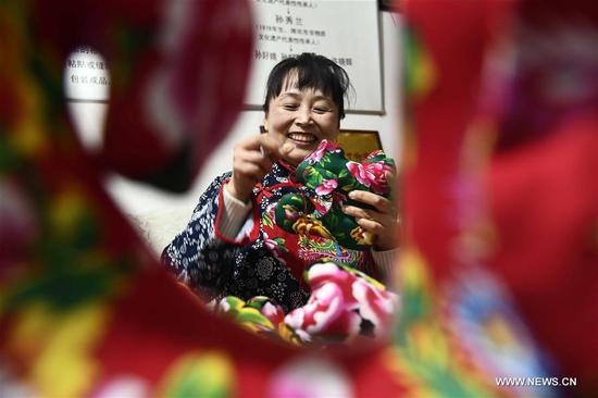 Sun Xiulan, an inheritor of intangible cultural heritage, makes a cloth toy at a workshop at the Yangjiabu folk art grand view park at Weifang City, east China's Shandong Province, March 7, 2018. The female inheritors at the park keep on working and wrote down their wishes to celebrate the International Women's Day. (Xinhua/Guo Xulei)