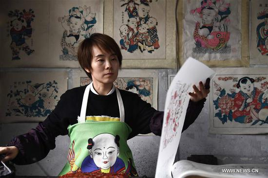 Yang Jing, an inheritor of intangible cultural heritage, makes new year paintings at a workshop at the Yangjiabu folk art grand view park at Weifang City, east China's Shandong Province, March 7, 2018. The female inheritors at the park keep on working and wrote down their wishes to celebrate the International Women's Day. (Xinhua/Guo Xulei)