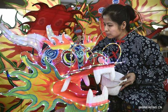 Tian Xifang, an inheritor of intangible cultural heritage, makes a kite with dragon head at a workshop at the Yangjiabu folk art grand view park at Weifang City, east China's Shandong Province, March 7, 2018. The female inheritors at the park keep on working and wrote down their wishes to celebrate the International Women's Day. (Xinhua/Guo Xulei)