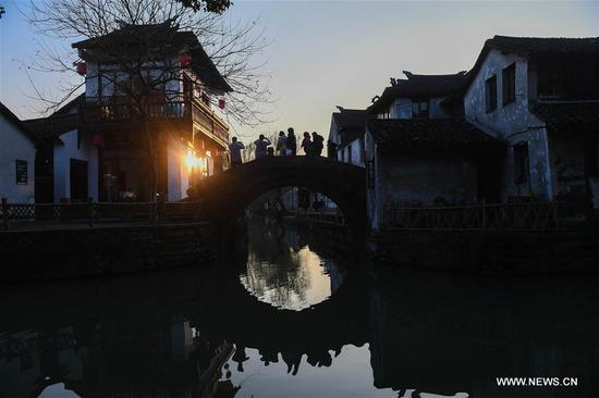 Tourists walk on a bridge in the ancient town of Zhouzhuang in Suzhou City, east China's Jiangsu Province, March 9, 2018. As temperature rises, the water town of Zhouzhuang becomes hot tourist destination. (Xinhua/Ji Chunpeng)