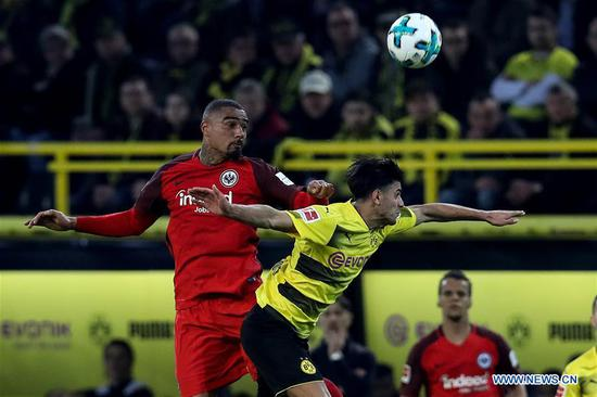 Mahmoud Dahoud (R) of Dortmund vies with Kevin-Prince Boateng of Frankfurt during the German Bundesliga soccer match between Borussia Dortmund and Eintracht Frankfurt in Dortmund, Germany, on March 11, 2018. Dortmund won 3-2. (Xinhua/Joachim Bywaletz)