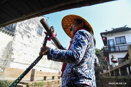 A barge-woman rows a sightseeing boat on the river in the ancient town of Zhouzhuang in Suzhou City, east China's Jiangsu Province, March 10, 2018. As temperature rises, the water town of Zhouzhuang becomes hot tourist destination. (Xinhua/Ji Chunpeng)