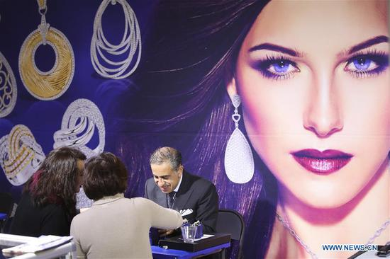 A sales person (1st R) introduces products to buyers at a booth at the JA New York Spring Show in New York, the United States, March 12, 2018. The JA New York Spring Show which lasts from March 11 to March 13 attracts about 400 exhibitors and retailers around the world this year. The JA New York jewelry show is a leading international jewelry event and is held three times a year in New York City. (Xinhua/Wang Ying)