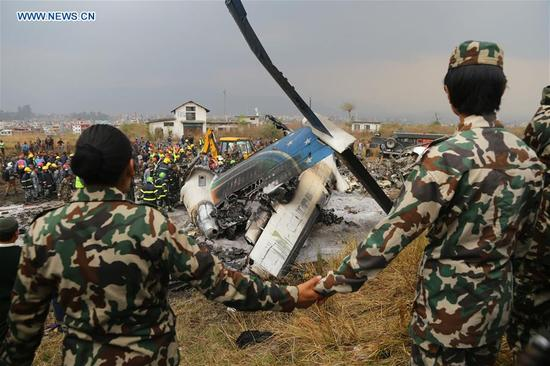 Security personnel guard near the plane crash site in Kathmandu, Nepal, on March 12, 2018. At least 49 people were killed and 17 injured after a passenger plane of the US-Bangla Airlines crashed at Nepal's Tribhuvan International Airport (TIA) on Monday afternoon, authorities confirmed. (Xinhua/Sunil Sharma)