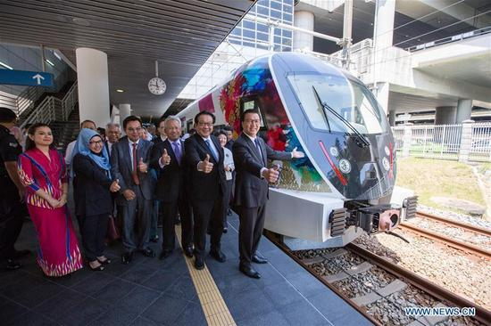 Malaysian Transport Minister Liow Tiong Lai (1st R) and guests pose for photos with the new KLIA Ekspres train at the Kuala Lumpur International Airport in Sepang, Malaysia, on March 13, 2018. China's CRRC Changchun Railway Vehicles Co. Ltd (CRRC Changchun) and Malaysia's Express Rail Link (ERL) unveiled the new train that will be used for the Kuala Lumpur International Airport rail link service on Tuesday, concluding a deal signed in 2014 in which ERL agreed to buy six trains from CRRC Changchun. (Xinhua/Zhu Wei)