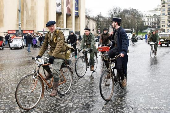 Cyclists ride vintage bikes past the Trocadero Square in Paris, France on Jan. 7, 2018. Hundreds of vintage cars, racing cars, jeeps, buses, motorcycles and bikes participated on Sunday in the 18th Paris Crossing of Classic Cars. (Xinhua/Chen Yichen)
