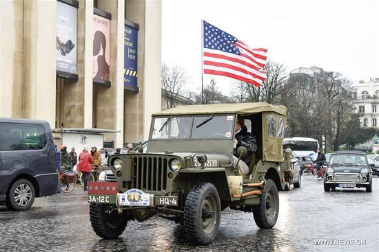 A vintage jeep with a flag of the U.S. passes the Trocadero Square in Paris, France on Jan. 7, 2018. Hundreds of vintage cars, racing cars, jeeps, buses, motorcycles and bikes participated on Sunday in the 18th Paris Crossing of Classic Cars. (Xinhua/Chen Yichen)