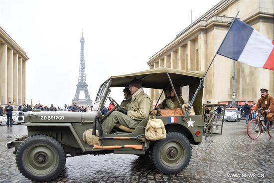 A vintage jeep with a flag of France passes the Trocadero Square in Paris, France on Jan. 7, 2018. Hundreds of vintage cars, racing cars, jeeps, buses, motorcycles and bikes participated on Sunday in the 18th Paris Crossing of Classic Cars. (Xinhua/Chen Yichen)