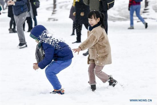 Chinese tourists have a snowball fight on the Concorde Square in Paris, France on Feb. 7, 2018. A snap cold and intensified snowfall hit Paris and its surrounding areas.(Xinhua/Chen Yichen)
