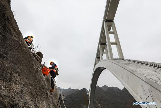 Bridge maintenance workers work at the Beipanjiang railway bridge in southwest China's Guizhou Province, Jan. 26, 2018. The high-speed railway bridge, 721 meters in length, is a part of the Shanghai-Kunming high-speed railway line, which links the country's prosperous eastern coast with the less-developed southwest. Maintenance workers examine the bridge everyday to make sure the safety of the railway line. (Xinhua/Liu Xu)