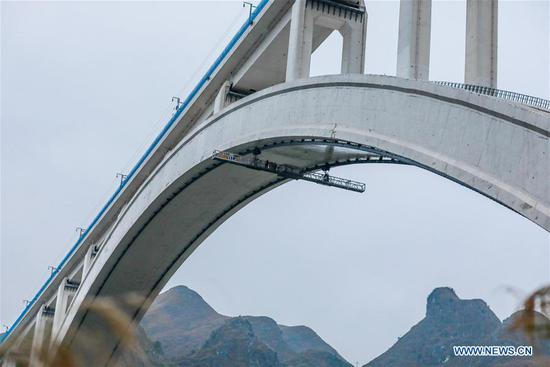 Bridge maintenance workers work under the arch of the Beipanjiang railway bridge in southwest China's Guizhou Province, Jan. 26, 2018. The high-speed railway bridge, 721 meters in length, is a part of the Shanghai-Kunming high-speed railway line, which links the country's prosperous eastern coast with the less-developed southwest. Maintenance workers examine the bridge everyday to make sure the safety of the railway line. (Xinhua/Liu Xu)