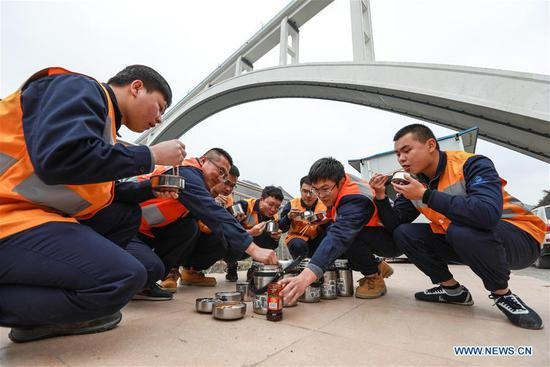 Bridge maintenance workers have meals on the Beipanjiang railway bridge in southwest China's Guizhou Province, Jan. 26, 2018. The high-speed railway bridge, 721 meters in length, is a part of the Shanghai-Kunming high-speed railway line, which links the country's prosperous eastern coast with the less-developed southwest. Maintenance workers examine the bridge everyday to make sure the safety of the railway line. (Xinhua/Liu Xu)