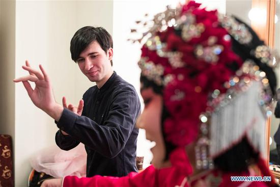 An actress teaches a Russian man gestures of Yuju Opera at China Cultural Center in Moscow, Russia, on March 5, 2018. Artists from China's Henan Yuju Opera Theater presented performances here on Monday. (Xinhua/Wu Zhuang)