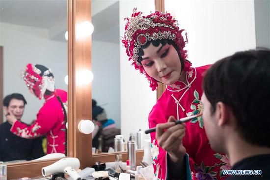 An actress helps a Russian man do make-up at China Cultural Center in Moscow, Russia, on March 5, 2018. Artists from China's Henan Yuju Opera Theater presented performances here on Monday. (Xinhua/Wu Zhuang)