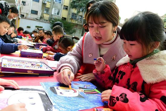 A child draws picture of her mother under the guidance of a volunteer during an activity ahead of the International Women's Day at Chaoyanglou kindergarten in Zhenjiang City, east China's Jiangsu Province, March 6, 2018. (Xinhua/Shi Yucheng)
