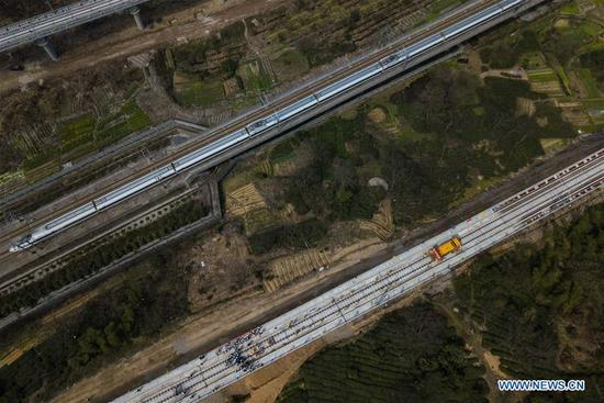 In this aerial photo taken on March 12, 2018, railway construction workers lay the tracks for the Hangzhou-Huangshan high-speed line (below) in Hangzhou, east China's Zhejiang Province. The Hangzhou-Huangshan high-speed line is scheduled to open in 2018. (Xinhua/Huang Zongzhi)