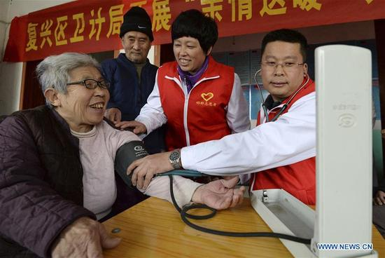 Volunteers check blood pressure for old people in Handan, north China's Hebei Province, Dec. 5, 2017, the international volunteer day. (Xinhua/Hao Qunying)