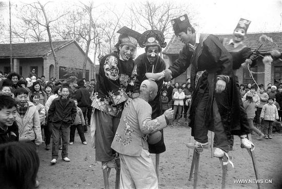 File photo taken in January 1992 shows folk artists exercising stilts in Linquan County of east China's Anhui Province. In Chinese villages, people have their distinctive ways to celebrate the Spring Festival. Simple but joyful, the celebrations bring them gratification and happiness. Spring festival, or better known as Chinese Lunar New year, is the most important festival for all Chinese, which has a history of more than 4,000 years. It is an occasion for home returning, New Year goods preparing, celebrating, and foremost, family reunion. (Xinhua/Chen Fei)