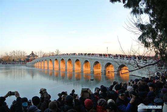 Visitors admire the scenery of twilight shining through the Seventeen Arch Bridge in the Summer Palace in Beijing, capital of China, Dec. 6, 2017. (Xinhua/Ma Zhihong)