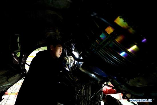 A technician examines the engine of an airplane in Harbin, northeast China's Heilongjiang Province, Feb. 10, 2018. About 50 technicians of Heilongjiang branch of China Southern Airlines are responsible for checking and maintaining airplanes to better cope with the upcoming Spring Festival travel rush. (Xinhua/Wang Kai)