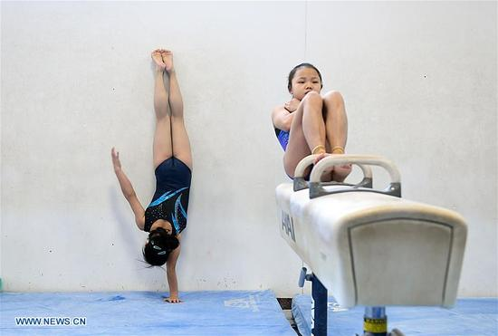Guan Chenchen(L) and Li Qi, members of China's women gymnastic team, are seen during training at Chow's Gymnastics and Dance Institute in West Des Moines, Iowa, the United States, on Dec. 27, 2017. Four Chinese women gymnasts have attended a 20-day training program since Dec. 11. (Xinhua/Yin Bogu)