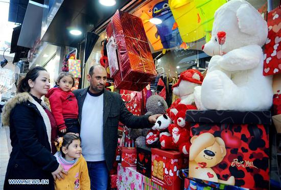 A family select gifts displayed at a shop a day ahead of the Valentine's Day in Damascus, capital of Syria, on Feb. 13, 2018. (Xinhua/Ammar Safarjalani)