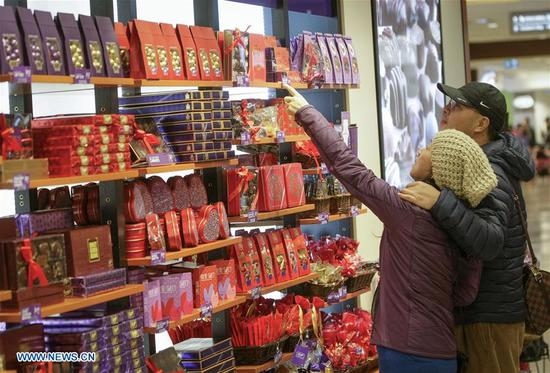Customers choose chocolates at a candy shop in Vancouver, Canada, on Feb. 13, 2018. Chocolate retailers in Vancouver prepared a variety of Valentine-themed products for the upcoming Valentine's Day. (Xinhua/Liang Sen)