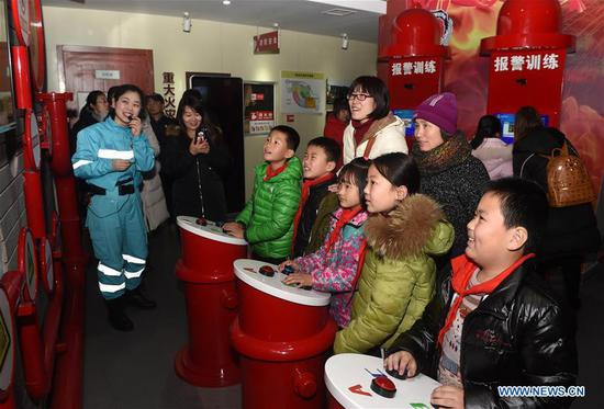 Children attend a lecture on fire safety at a home safety training center in Qingdao, east China's Shandong Province, March 7, 2018. The Qingdao Municipal Women's Federation organized a home safety workshop on Wednesday, allowing participants to learn home safety knowledge and skills via on-the-spot training sessions. (Xinhua/Li Ziheng)