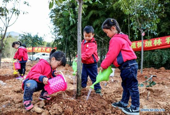 Children water a tree during a tree planting activity at Lijiaxiang Township of Changxing County, east China's Zhejiang Province, March 12, 2018. A tree planting activity aimed at fostering children's awareness about environmental protection was held here. (Xinhua/Xu Xu)