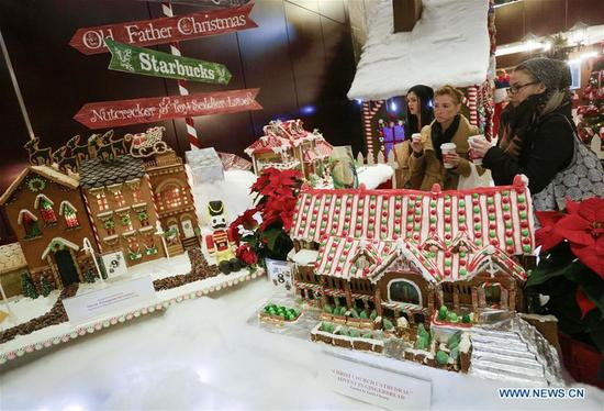 Visitors admire gingerbread houses displayed at the 27th annual Gingerbread Lane competition in Vancouver, Canada, Dec. 4, 2017. A total of 33 local amateur and professional cakemakers participated in the event and showed their works to visitors. (Xinhua/Liang Sen)