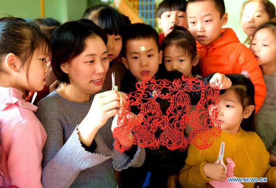 Children learn paper-cutting to greet the upcoming Chinese lunar New Year at a kindergarten in Hengshui City, north China's Hebei Province, Feb. 4, 2018. The Chinese lunar year for 2018 is the Year of the Dog and this year's Spring Festival falls on Feb. 16. (Xinhua/Wang Xiao)