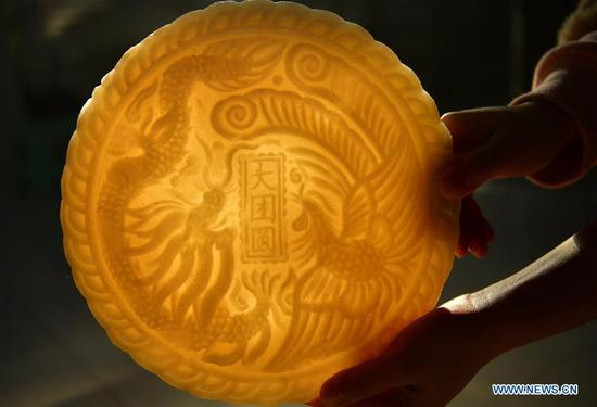 A villager shows Ciba, or glutinous rice cake, to greet the upcoming Spring Festival in Banchang Village of Xuan'en County, Enshi Tujia and Miao Autonomous Prefecture, central China's Hubei Province, Jan. 11, 2018. The handmade Ciba, usually decorated with patterns, is the traditional food for people of Tujia and other ethnic minorities on the Spring Festival, which falls on Feb. 16 this year. (Xinhua/Song Wen)