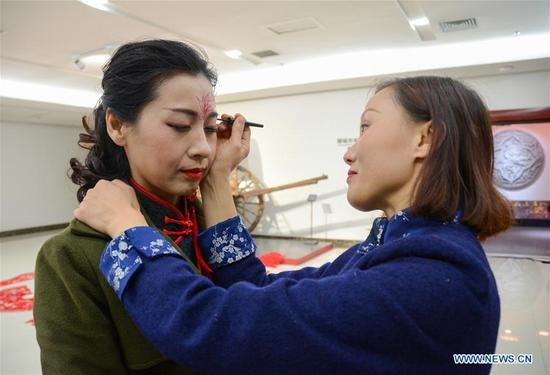 Liang Ying (R) puts on make-up for the cheongsam hobbyist in Liaocheng, east China's Shandong Province, Feb. 10, 2018. Liang Ying, provincial-level inheritor of traditional Chinese paper cutting, which is one of the intangible cultural heritages, designs paper cutting ornaments for the cheongsam, or qipao in Mandarin Chinese, to greet the Chinese lunar New Year. (Xinhua/Xu Wenhao)