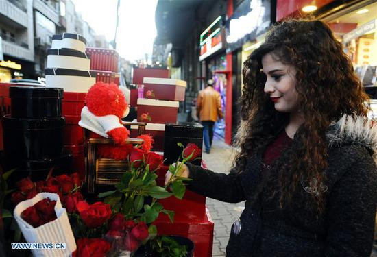 A woman picks a rose outside a shop a day ahead of the Valentine's Day in Damascus, capital of Syria, on Feb. 13, 2018. (Xinhua/Ammar Safarjalani)